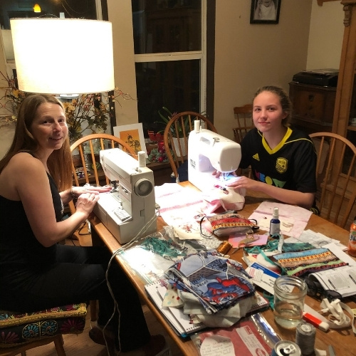 A mother and daughter at sewing machines making masks