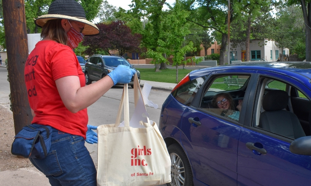 Girls Inc of Santa Fe delivers a tote bag of supplies to a girl in a car