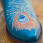 A blue cowboy boot with a peacock feather