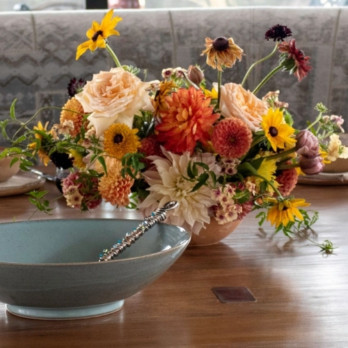 A fall floral arrangement and blue ceramic bowl