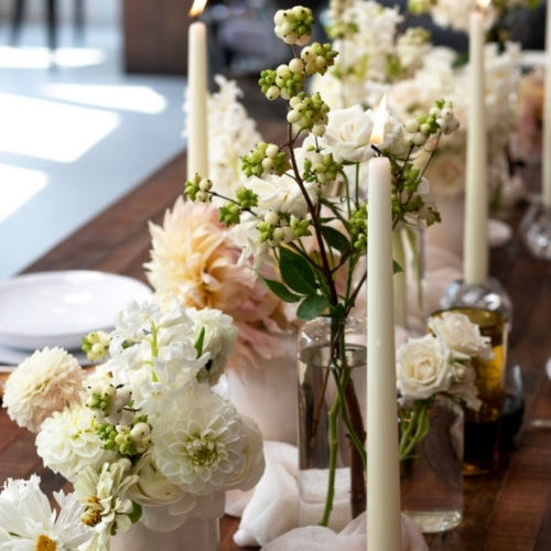 A pastel floral arrangement with long tapered candles