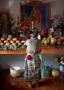 A woman stands in front of an ofrenda in rural Mexico