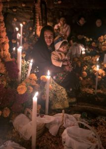A woman holding a child surrounded by candles in rural Mexico.