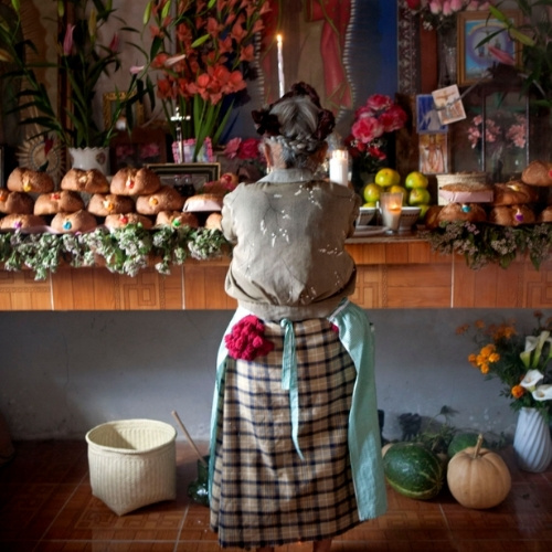 A woman in front of an ofrenda in rural Mexico.