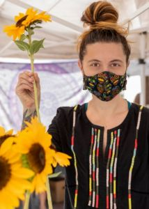 Kelly Haug, holding sunflowers while wearing a mask