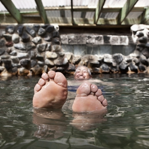 An older man's feet poke out of the water in a hot spring