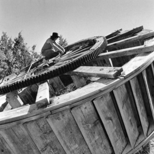 A worker on top of a horizontal water wheel