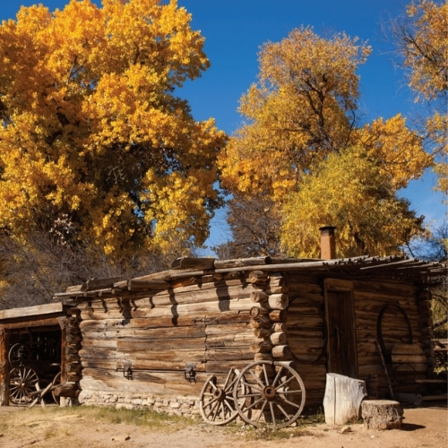 An old structure in New Mexico in front of fall foliage