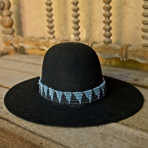A black hat with a blue and black patterned band