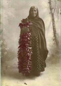 An antique photograph of a woman holding a chile ristra