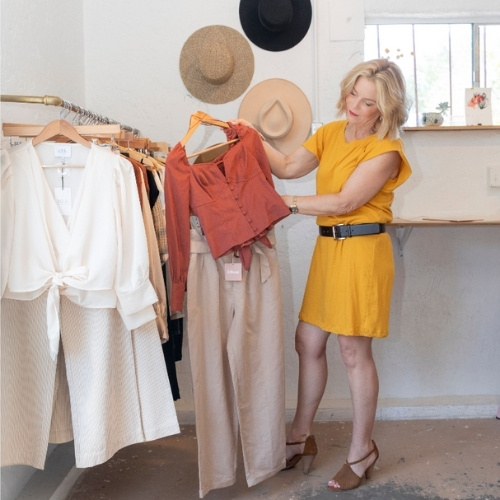 A woman in a yellow dress selecting an outfit to wear