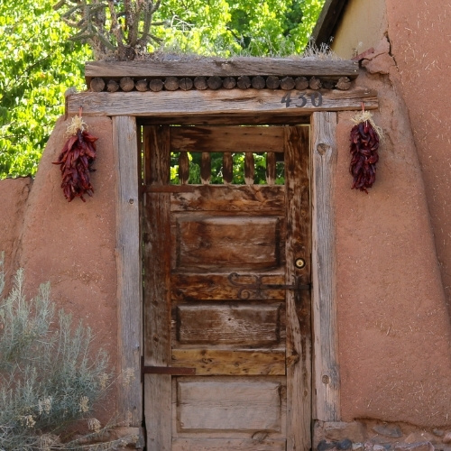 A door in an adobe wall with ristras