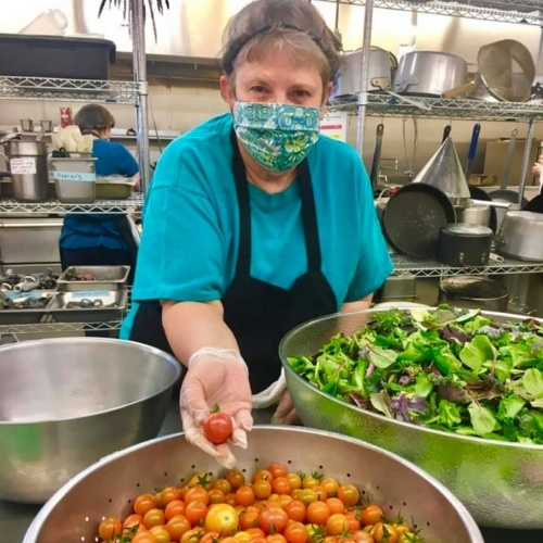 A woman in a mask prepares salad in a kitchen.