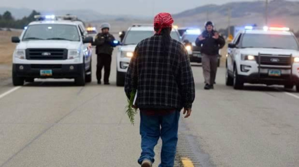 Ricardo Caté approaches police officers at Standing Rock