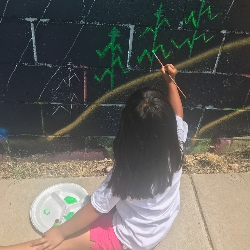 A young girl painting a mural in Santa Fe, New Mexico