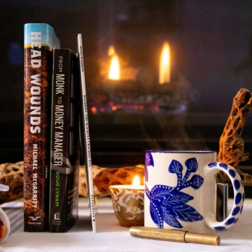 A group of books in front of a fire place.