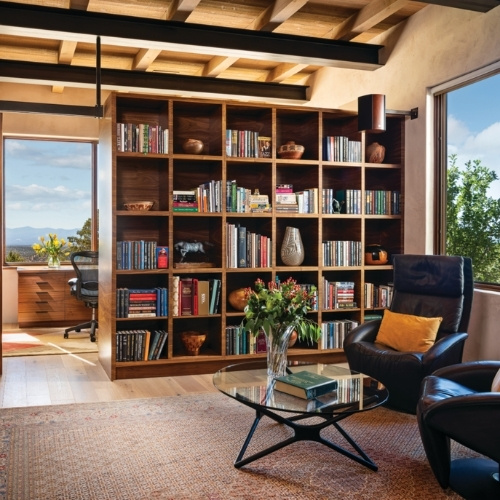 A double-sided, floor-to-ceiling bookcase separates a media room from an office/sewing room.
