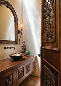 The powder room features a custom vanity carved by the talented craftsmen at Ernest Thompson